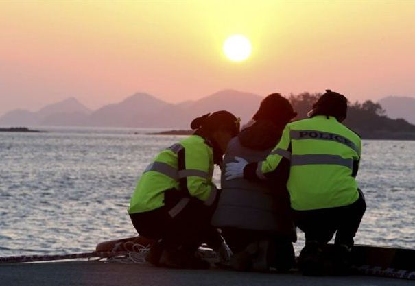 A relative, center, of a passenger aboard the sunken Sewol ferry is consoled by police officers as she awaits news on her missing loved one at a port in Jindo, South Korea, Wednesday, April 30, 2014. Two weeks after the ferry sank off South Korea's southern cost, divers have recovered over 200 bodies from the wreckage, but they fought strong currents and floating debris inside the ship Wednesday as they searched for 90 passengers still missing. (AP Photo/Yonhap) KOREA OUT (File: South Korea Ship Sinking.JPEG-0f735.jpg )