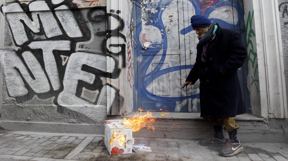 Αστεγος έχει βάλει φωτιά σε χαρτόκουτα για να ζεσταθεί, Αθήνα Τετάρτη 18 Φεβρουαρίου 2015. Η θερμοκρασία στην Αθήνα είναι 3 βαθμοί Κελσίου. Σύμφωνα με έρευνα του 2012 οι άστεγοι στην Αθήνα ήταν περίπου 9000 και στην πλειοψηφία τους δεν ήταν άστεγοι πριν την οικονομική κρίση.  ΑΠΕ-ΜΠΕ/ΑΠΕ-ΜΠΕ/ΟΡΕΣΤΗΣ ΠΑΝΑΓΙΩΤΟΥ