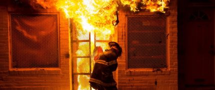 A firefighter uses a saw to open a metal gate while fighting a fire in a convenience store and residence during clashes after the funeral of Freddie Gray in Baltimore, Maryland in the early morning hours of April 28, 2015. Baltimore erupted in violence as hundreds of rioters looted stores, burned buildings and injured at least 15 police officers following the funeral of Gray, a 25-year-old black man who died after he was injured in police custody. REUTERS/Eric Thayer TPX IMAGES OF THE DAY